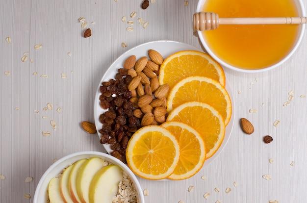 健康食品。フルーツ、ナッツ、白いテーブルの上の蜂蜜。フラットトップビュー