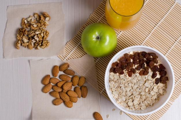 健康食品。白いテーブルにフルーツ、ナッツ、オートミール、オレンジジュース