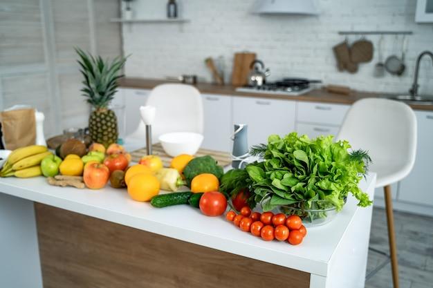 Здоровая пища, фрукты, овощи, ягоды, листовые овощи на столе на фоне кухни