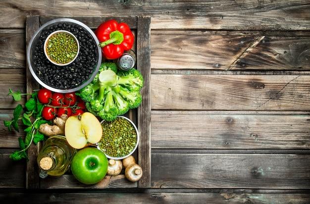 健康食品。マメ科植物と野菜や果物の健康的な品揃え。木製の背景に。