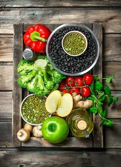 健康食品。木製のテーブルにマメ科植物と野菜や果物の健康的な品揃え。