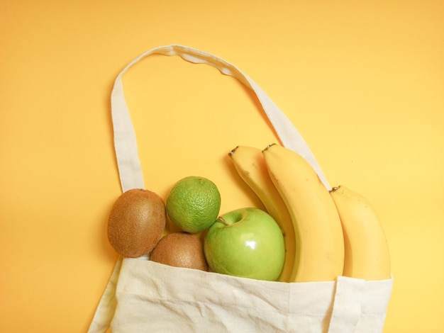 Healthy food. healthy fruits in natural bag on yellow.