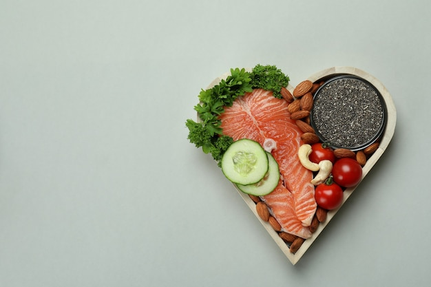 Healthy food in heart on light gray background