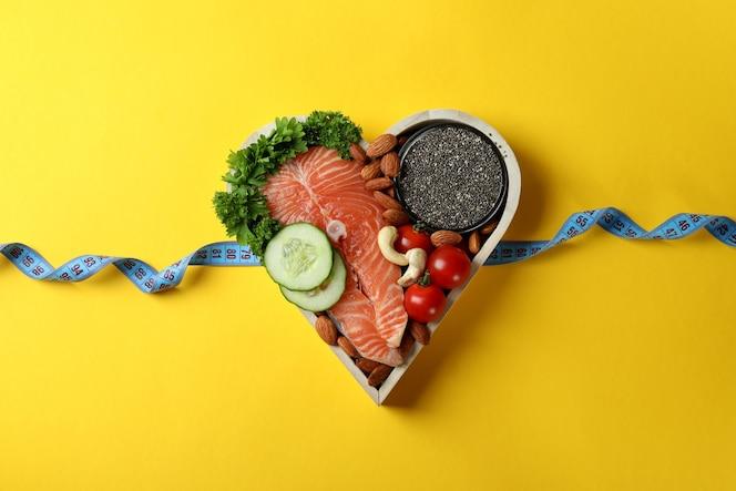 cibo sano nel cuore e nastro di misurazione su sfondo giallo