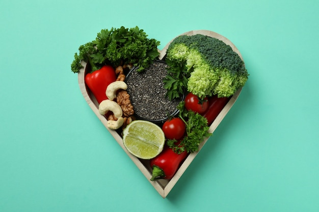Healthy food in heart on mint background, top view