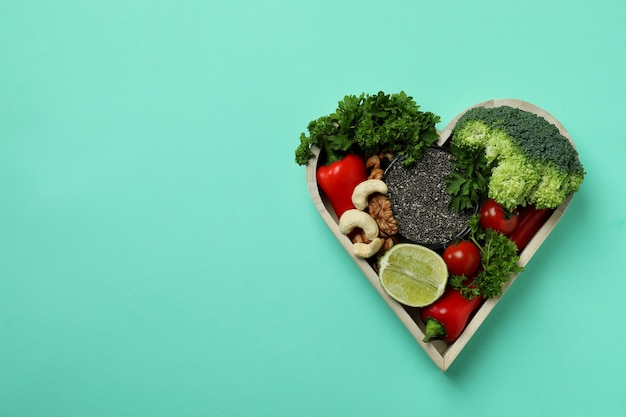 Healthy food in heart on mint background