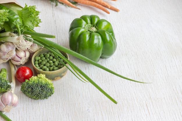 Здоровая еда в бумажном пакете разных овощей на белом столе. вид сверху