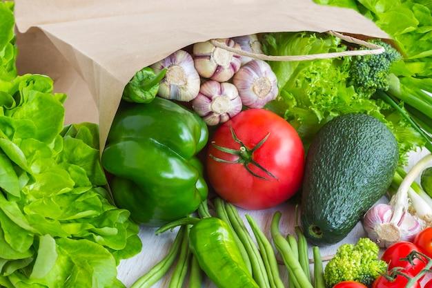 Здоровое питание в бумажном пакете разных овощей на белом. вид сверху