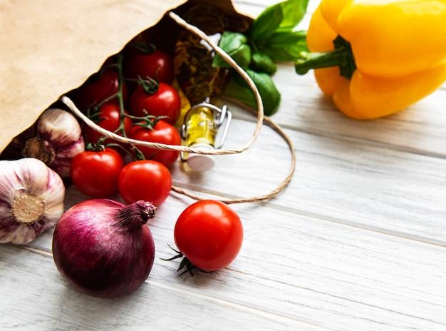 Здоровая пища в бумажном пакете на белой деревянной поверхности
