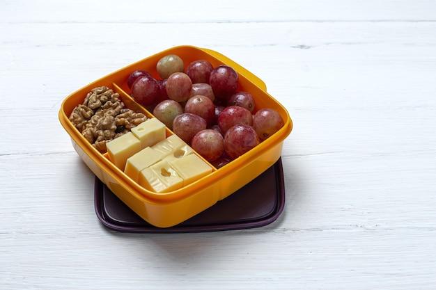 Здоровая пища в пластиковом контейнере, готовая к употреблению с сыром, виноградом и грецкими орехами на столе