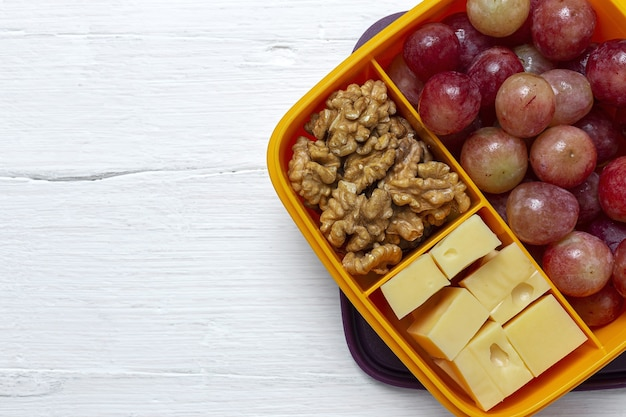 테이블에 치즈, 포도, 호두와 함께 먹을 준비가 된 플라스틱 용기의 건강 식품