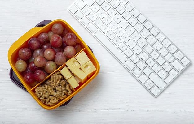 Здоровое питание в пластиковом контейнере готово к употреблению с сыром, виноградом и грецкими орехами на рабочем столе