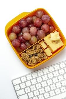 작업 테이블에 치즈, 포도, 호두와 함께 먹을 준비가 된 플라스틱 용기의 건강 식품. 빼앗 으려면 호두. 외딴