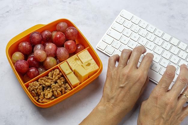 작업 테이블에 치즈, 포도, 호두와 함께 먹을 준비가 된 플라스틱 용기의 건강 식품. 빼앗기 다. 호두