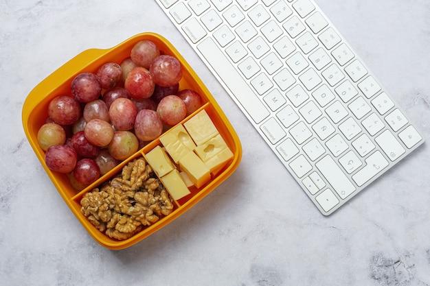 作業台の上でチーズ、ブドウ、クルミと一緒に食べる準備ができているプラスチック容器の健康食品。クルミを奪う