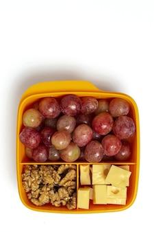 작업 테이블에 치즈, 포도 및 호두와 함께 먹을 준비가 된 플라스틱 용기의 건강 식품