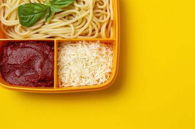 作業台にトマト、チーズ、バジルを添えた自家製スパゲッティと一緒に食べる準備ができているプラスチック容器に入った健康食品。イタリア料理。持ち帰る。