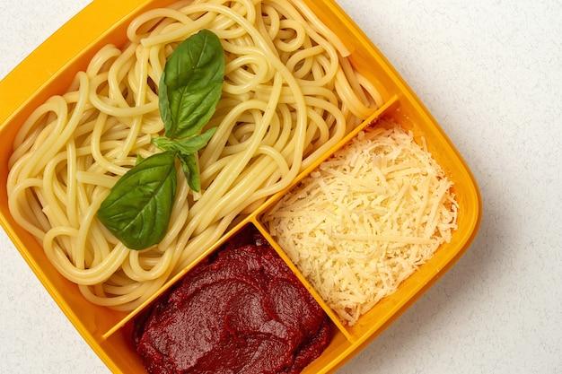 Здоровая еда в пластиковых контейнерах, готовая к употреблению с домашними спагетти с помидорами, сыром и базиликом на рабочем столе. итальянская еда. забрать.