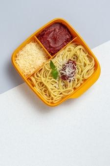 작업 테이블에 토마토, 치즈, 바질과 함께 만든 스파게티와 함께 먹을 준비가 플라스틱 용기에 건강 식품. 이탈리아 음식. 빼앗아.