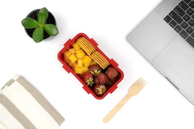 Здоровое питание на рабочем месте в офисе. веганский обед-бокс на рабочем месте с ноутбуком.