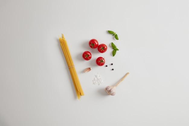 健康食品成分。パスタを作るための小麦スパゲッティ、海塩、トマト、ニンニク、コショウの実、バジルの束。白い背景、上からの眺め。料理、イタリア料理、ベジタリアンのコンセプト
