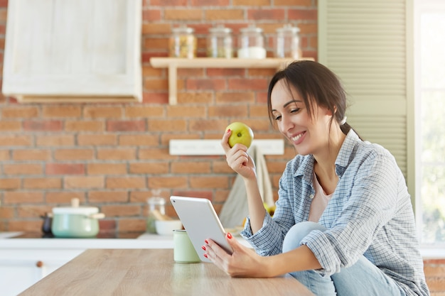 Healthy food and lifestyle concept. pretty female eats apple, looks for new diet in internet,