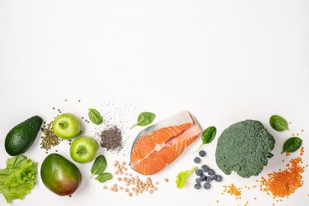 흰색 배경에 연어, 콩과 식물, 치아 씨앗, 야채 및 과일과 같은 건강 식품