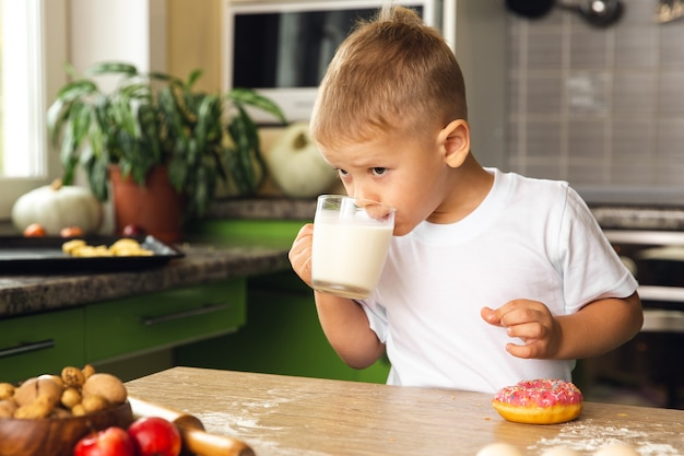 건강한 음식. 작은 아이 소년 우유를 마시고 부엌에서 도넛을 먹고