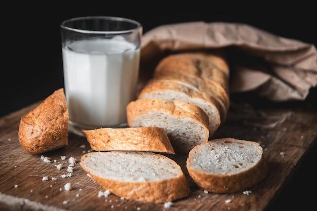 건강한 음식. 두 개의 잘린 조각이 있는 긴 시골 빵 한 덩어리가 나무 도마와 신선한 우유 한 잔 위에 놓여 있습니다. 어두운 배경입니다. 가로 샷