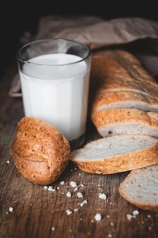 건강한 음식. 두 개의 잘린 조각이 있는 긴 시골 빵 한 덩어리가 나무 도마와 신선한 우유 한 잔 위에 놓여 있습니다. 어두운 배경입니다.