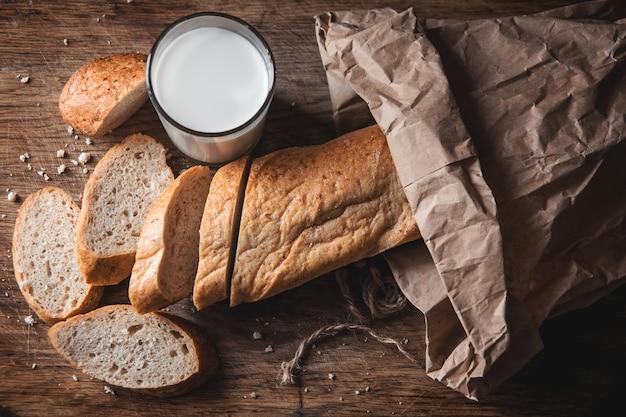 건강한 음식. 두 개의 잘린 조각이 있는 긴 시골 빵 한 덩어리가 나무 도마와 신선한 우유 한 잔 위에 놓여 있습니다.