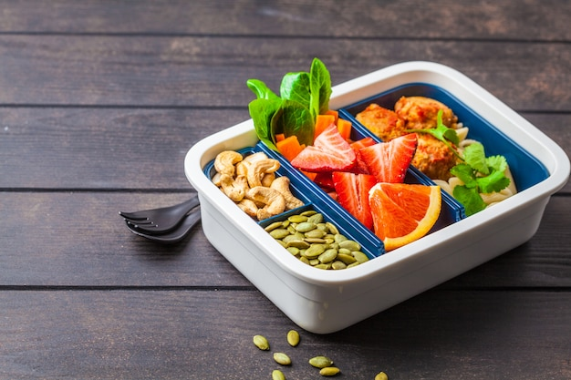 Healthy food lunch box. vegan food: beans meatballs, pasta, vegetables, berries, seeds and nuts in a container