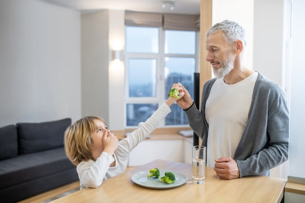 Здоровая пища. зрелый мужчина и его сын завтракают вместе