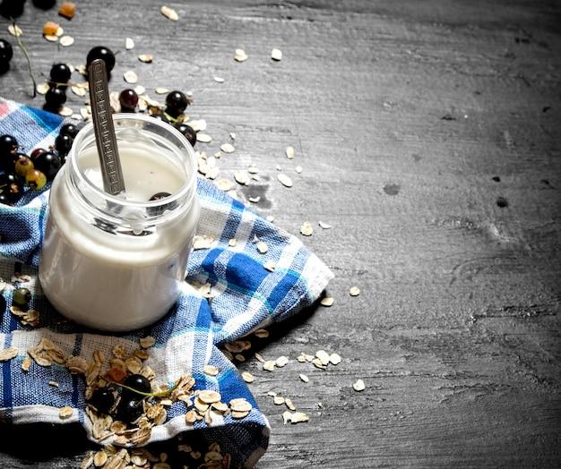 Здоровая пища. крем молочный с овсом и черной смородиной. на черном деревянном фоне.