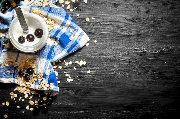 健康食品。黒い木製のテーブルにオート麦と野生の黒スグリのミルククリーム。