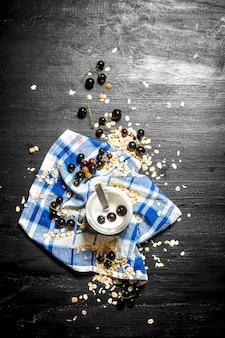 Здоровая пища. молочный крем с овсом и дикой черной смородиной на черном деревянном столе.