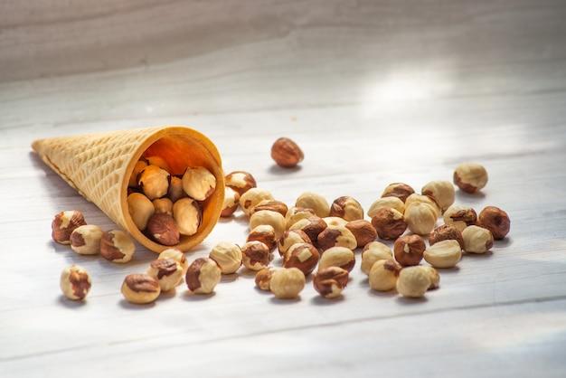 건강 식품 믹스 견과류 말린 과일 땅콩 헤이즐넛 호두 자두 삼베 나무 배경에 말린 살구를 닫습니다