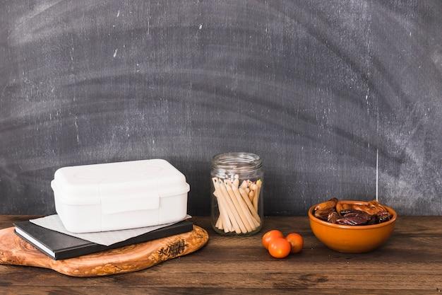 Cibo sano vicino a pranzo e materiale scolastico