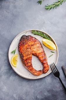 健康食品のオメガのコンセプトです。サーモンステーキのグリルレモン、ローズマリー、灰色の石の白い皿の上