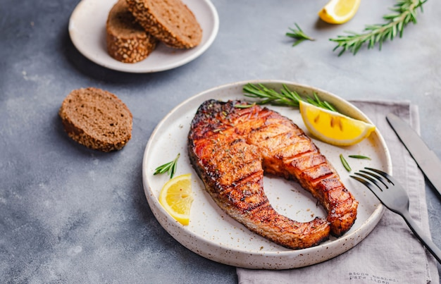 Healthy food omega concept. grilled salmon steak with lemon, rosemary served on white plate on gray stone
