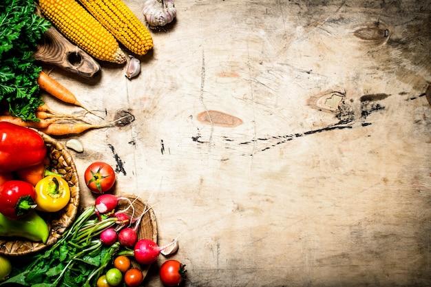 健康食品。有機野菜。ハーブと新鮮な野菜。木製の背景に。