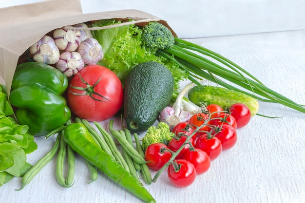 Healthy food in paper bag of different vegetables on white. top view
