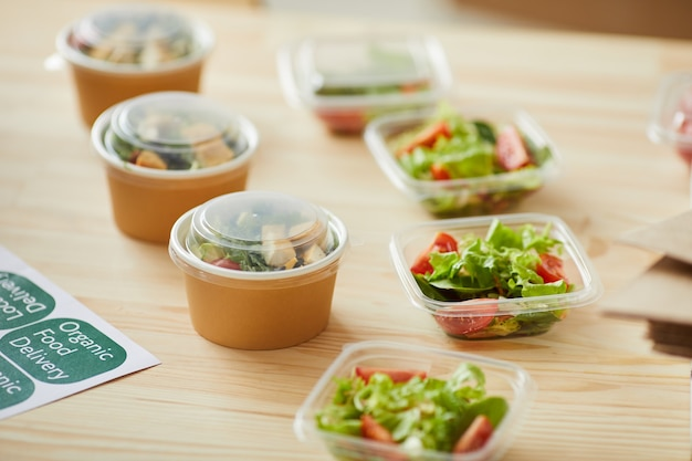 Healthy food portions ready for packaging on wooden table in small food delivery service