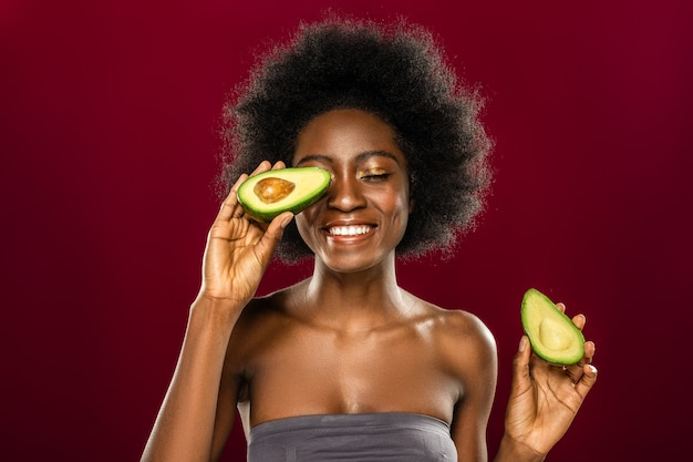 Здоровая пища. положительная счастливая женщина улыбается, прикладывая половину авокадо к глазу