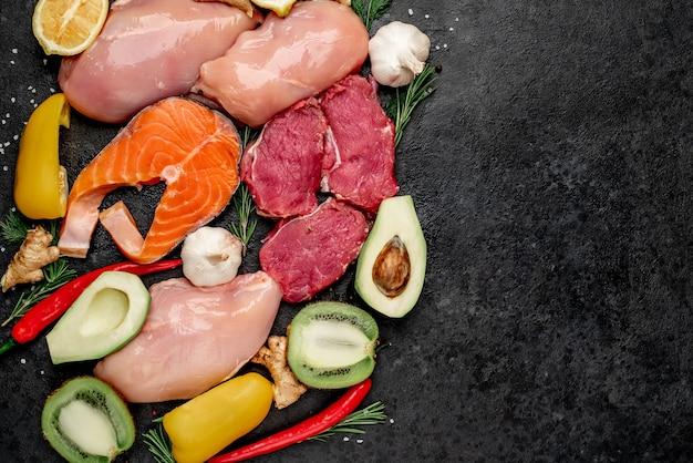Здоровое питание - сырая говядина, лосось, куриное филе, фрукты и овощи.