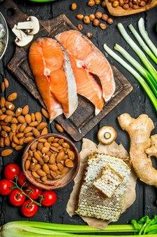 健康食品。有機食品を使った生鮭。黒の素朴なテーブルの上。