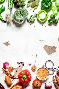 Здоровое питание сырые овощи, нарезанные ломтиками с чечевицей и зеленым горошком на деревенском фоне