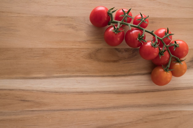 Healthy food. red ripe organic tomatoes on branch on wooden board. copy space for text.