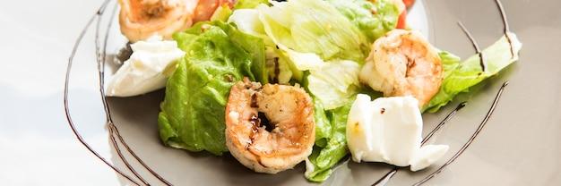 健康食品、サラダ、エビとチェリートマトのルッコラ、パルメザンチーズ、プレートでのクローズアップで覆われています。ケトダイエット
