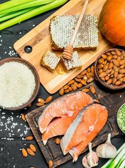 健康食品。黒の素朴なテーブルに蜂蜜と有機食品を添えたサーモンステーキ。